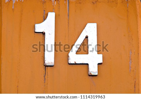number fourteen on orange wall #1114319963