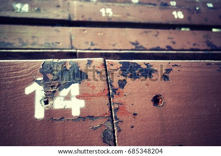Number fourteen painted on an old wooden seat, conceptual picture with copy space on the right. #685348204
