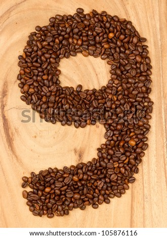 Number from coffee beans, isolated on wood