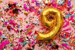Number 9 gold birthday celebration balloon on a confetti glitter background