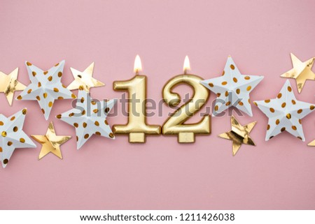 Number 12 Gold Candle And Stars On A Pastel Pink Background 1211426038