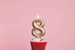Number 8 gold candle in a cupcake against a pastel pink background