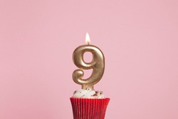 Number 9 gold candle in a cupcake against a pastel pink background