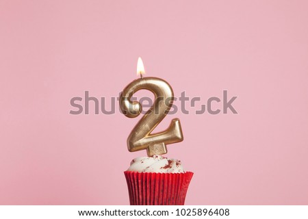 Photo of  Number 2 gold candle in a cupcake against a pastel pink background