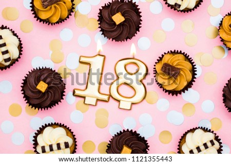 Number 18 gold candle with cupcakes against a pastel pink background