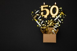 Number 50 gold celebration candle and gift box background