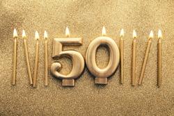 Number 50 gold celebration candle on a glitter background