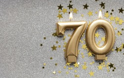 Number 70 gold celebration candle on star and glitter background