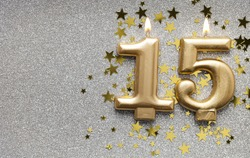 Number 15 gold celebration candle on star and glitter background