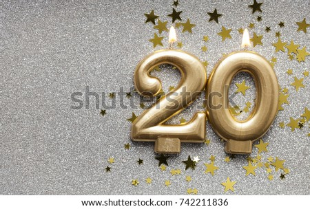 Number 20 gold celebration candle on star and glitter background #742211836