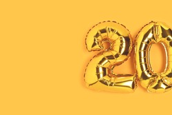 Number 20 golden balloons with copy space. Twenty years anniversary celebration minimalist concept on a yellow background.