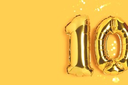 Number 10 golden balloons with gold bokeh. Ten years anniversary celebration concept on a yellow background.