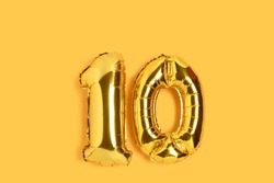 Number 10 golden balloons with place for text. Ten years anniversary celebration concept on a yellow background.