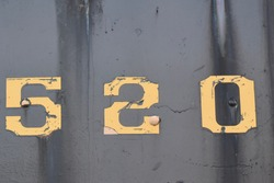 number 5 2 0 in yellow on black background with rust