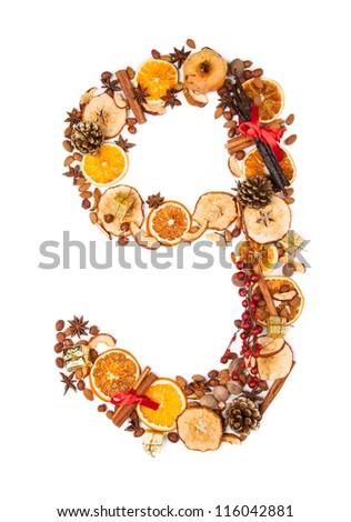 "Number ""9"" made of Christmas spices, dry orange and apple slices and small gifts. Isolated on white background"