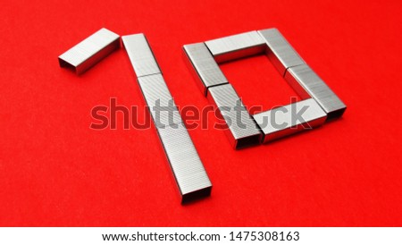 number made with stapler pins isolated on red background #1475308163