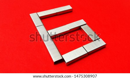 number made with stapler pins isolated on red background #1475308907