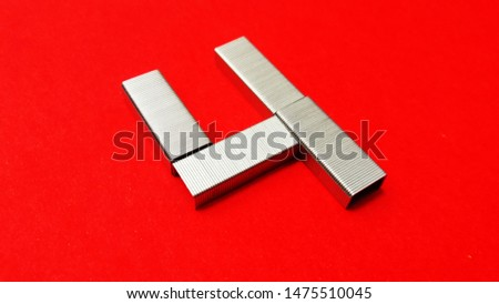 number made with stapler pins isolated on red background #1475510045