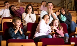Number of people and children enjoying scary film in in cinema house