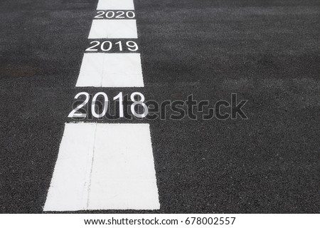 Number of 2018 to 2020 on asphalt road surface with marking lines, happy new year concept #678002557