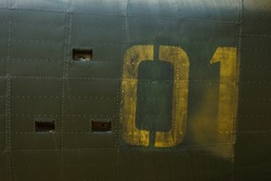 Number on a military aircraft fuselage. Texture. Old camouflage surface with exfoliated paint and rivets on a military aircraft.