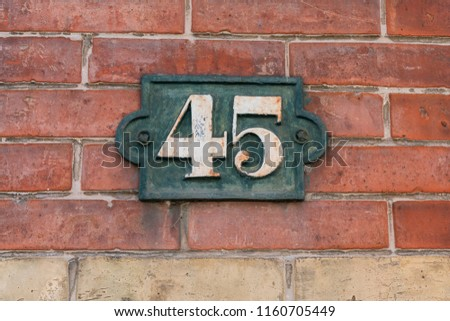 number 45 on a stone wall for the indication of house number