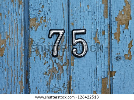 number 75 on blue wooden wall, close-up - stock photo