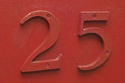 Number 25 on front door painted red.