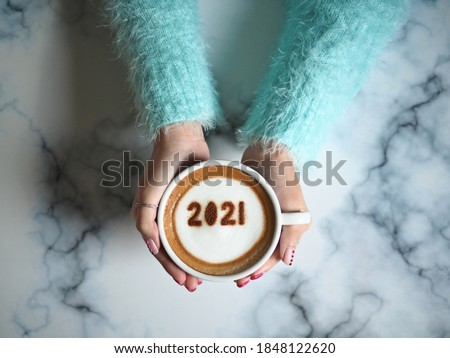 Number 2021 on frothy surface of cappuccino served in coffee cup holding by female hands with acrylic paint nail polish. Holidays food art theme for New Year 2021 celebration. (selective focus)