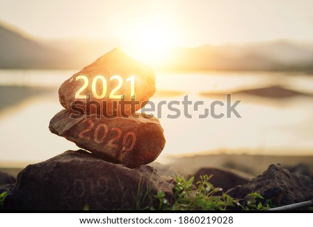 Number 2021 on stone the beach at sunrise. Concept Happy new year.