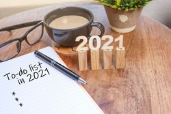 Number 2021 on the wooden sticks with a pen on the notebook with message on To-do List and eyeglasses and a cup of coffee