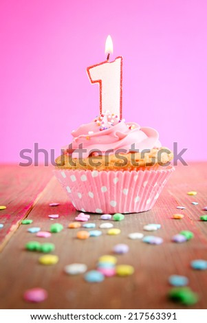 Number One Birthday Candle On A Pink Cupcake Wooden Table