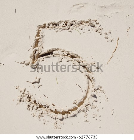 Number 5. Sand Alphabet: digits. Concept holiday background.