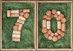 Number 70 seventy  made of wine corks on green background in wooden box