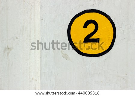 Number 2 sign painted on a white wall in yellow and black color #440005318