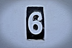 Number 6, six, white digit on a black tile, vignetted and subdued.