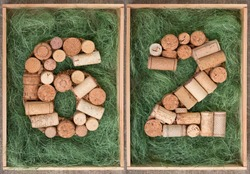 Number 62  sixty two  made of wine corks on green background in wooden box