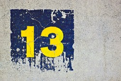 Number 13, thirteen, lucky or unlucky number, yellow and blue on plain background.