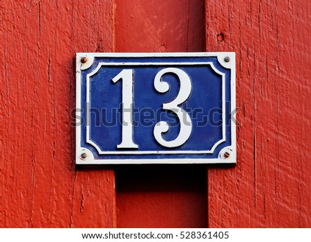 Number thirteen sign on a red wooden wall. #528361405