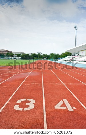 Number three and four on the start of a running track - stock photo