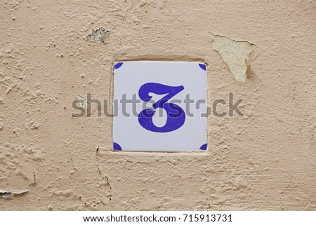 Number three information on a wall, detail of odd number, direction
