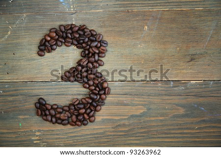 Number three made with coffee beans on a wooden plank