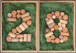 Number 28 twenty eight  made of wine corks on green background in wooden box