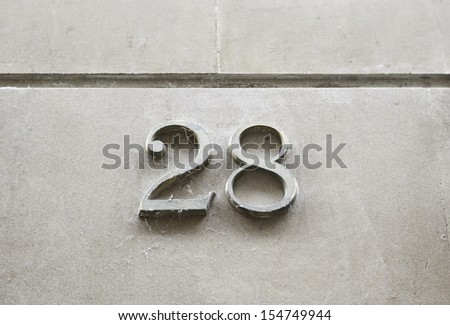 Number twenty-eight on the wall, detail of a number of information on a street, numbers