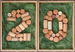 Number 20 twenty  made of wine corks on green background in wooden box