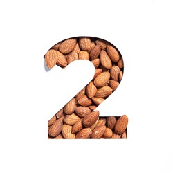 Number two made of almonds and paper cut in shape of second numeral isolated on white. Typeface of nutritious nuts