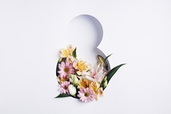 Number 8 with fresh spring flowers with green leaves on bright white background. Minimal Women's day, March 8th or birthday concept. Flat lay, top view.