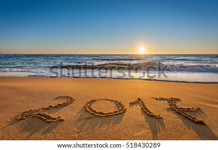 Number 2017 written on seashore sand at sunrise. Concept of upcoming new year and passing of time. #518430289