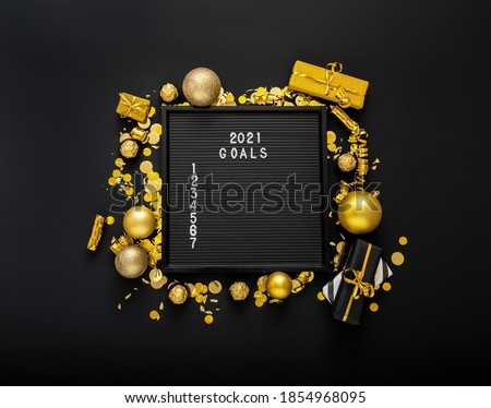 Numbered list of 2021 Goals on black Board in frame made of gold festive decor, gift boxes, confetti. New year eve 2021 goals, resolution check list with motivation or wishlist. Flat lay square