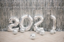 Numbers 2021 from silver colored balls against a silver wall. New Year